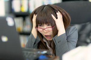 FXで損失を抱えて頭を抱えている女子